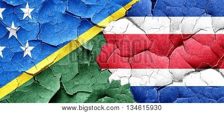 Solomon islands flag with Costa Rica flag on a grunge cracked wa