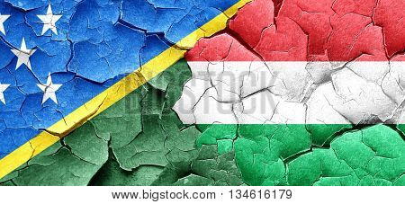 Solomon islands flag with Hungary flag on a grunge cracked wall