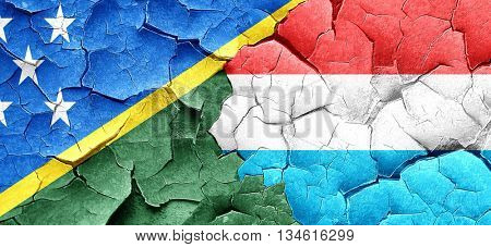 Solomon islands flag with Luxembourg flag on a grunge cracked wa