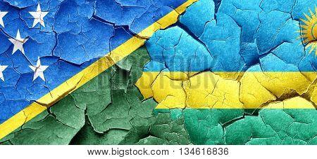 Solomon islands flag with rwanda flag on a grunge cracked wall