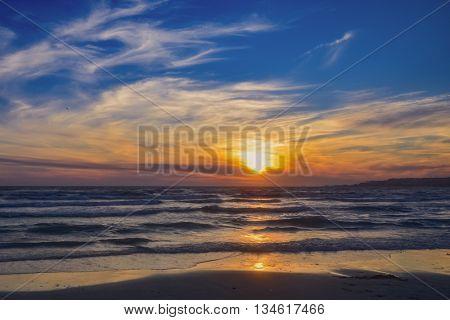Sunset over the sea beach sea and sun orange colors.