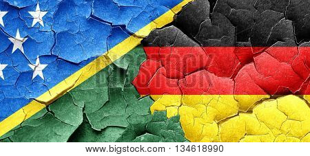 Solomon islands flag with Germany flag on a grunge cracked wall