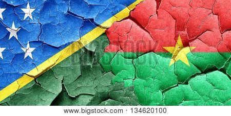 Solomon islands flag with Burkina Faso flag on a grunge cracked