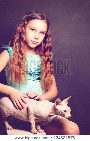 Young Girl holding hairless Cat on Background