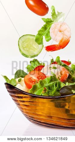 fresh green salad with shrimp on white background