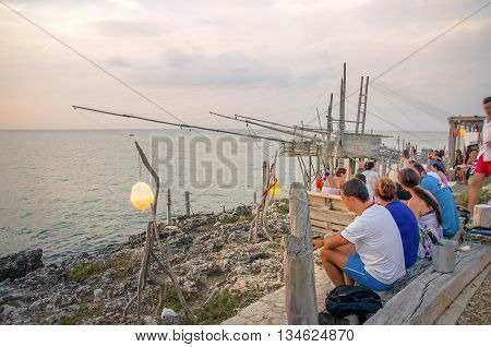 Peschici Italy August 21 2014: people get an aperitif drink on the sea during sunset near a traditional fishing machine called Trabucco
