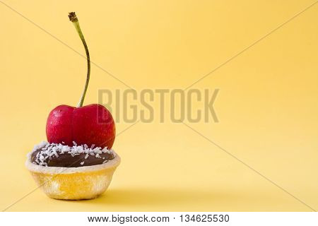 Delicious chocolate tartlets with cherry and coconut on yellow background