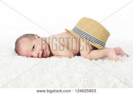 An adorable newborn smiling at the viewer as he lays on his belly on a fluffy white blanket with a straw fedora style hat on his behind.  On a white background.