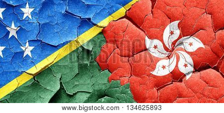 Solomon islands flag with Hong Kong flag on a grunge cracked wal