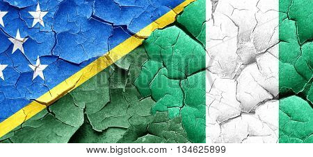 Solomon islands flag with Nigeria flag on a grunge cracked wall