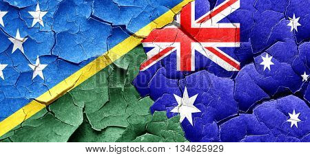 Solomon islands flag with Australia flag on a grunge cracked wal