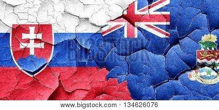 Slovakia flag with Cayman islands flag on a grunge cracked wall