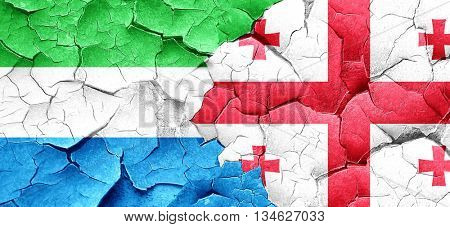 Sierra Leone flag with Georgia flag on a grunge cracked wall