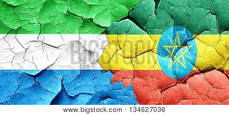 Sierra Leone flag with Ethiopia flag on a grunge cracked wall