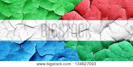 Sierra Leone flag with Hungary flag on a grunge cracked wall
