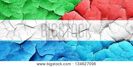 Sierra Leone flag with Luxembourg flag on a grunge cracked wall