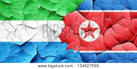 Sierra Leone flag with North Korea flag on a grunge cracked wall