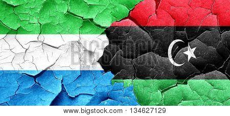 Sierra Leone flag with Libya flag on a grunge cracked wall