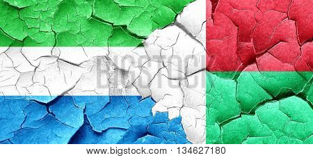 Sierra Leone flag with Madagascar flag on a grunge cracked wall