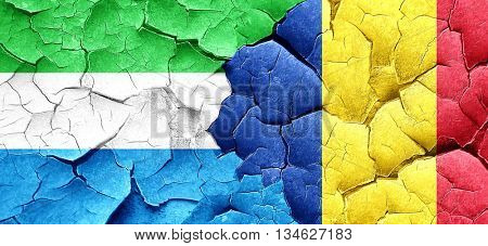 Sierra Leone flag with Romania flag on a grunge cracked wall