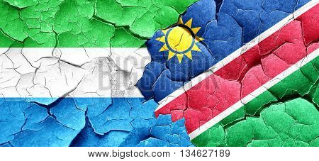 Sierra Leone flag with Namibia flag on a grunge cracked wall