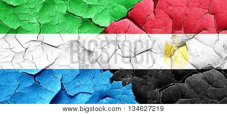 Sierra Leone flag with egypt flag on a grunge cracked wall