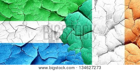 Sierra Leone flag with Ireland flag on a grunge cracked wall