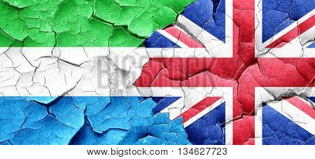 Sierra Leone flag with Great Britain flag on a grunge cracked wa