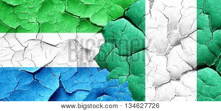 Sierra Leone flag with Nigeria flag on a grunge cracked wall