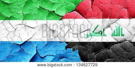 Sierra Leone flag with Iraq flag on a grunge cracked wall