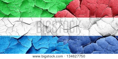 Sierra Leone flag with Netherlands flag on a grunge cracked wall