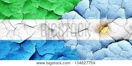 Sierra Leone flag with Argentine flag on a grunge cracked wall
