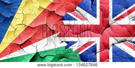 seychelles flag with Great Britain flag on a grunge cracked wall