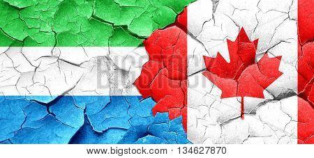 Sierra Leone flag with Canada flag on a grunge cracked wall