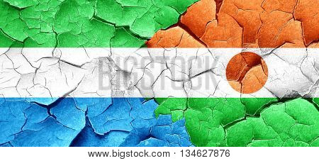Sierra Leone flag with Niger flag on a grunge cracked wall