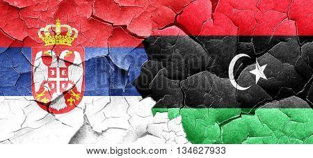 Serbia flag with Libya flag on a grunge cracked wall