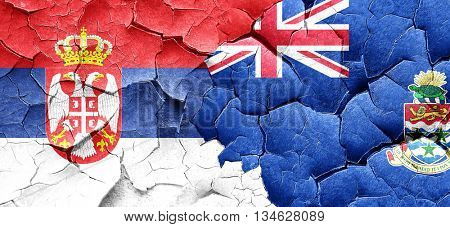 Serbia flag with Cayman islands flag on a grunge cracked wall
