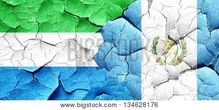 Sierra Leone flag with Guatemala flag on a grunge cracked wall