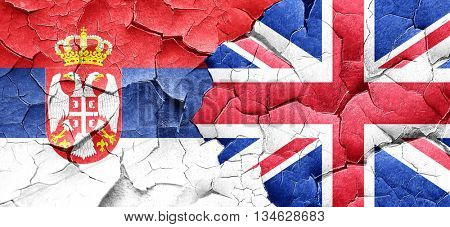 Serbia flag with Great Britain flag on a grunge cracked wall