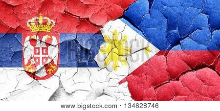 Serbia flag with Philippines flag on a grunge cracked wall