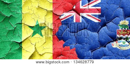 Senegal flag with Cayman islands flag on a grunge cracked wall
