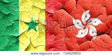 Senegal flag with Hong Kong flag on a grunge cracked wall