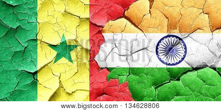 Senegal flag with India flag on a grunge cracked wall