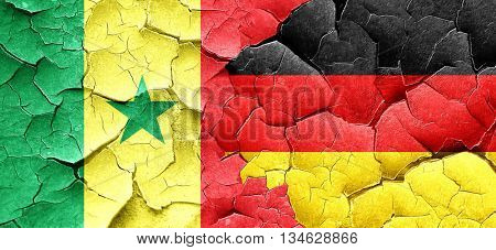 Senegal flag with Germany flag on a grunge cracked wall