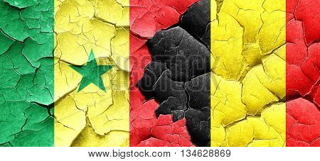 Senegal flag with Belgium flag on a grunge cracked wall