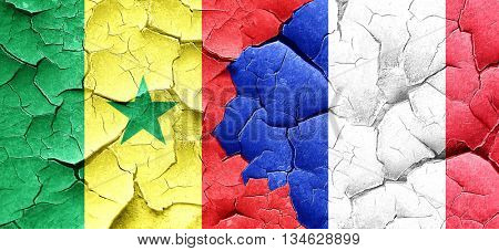 Senegal flag with France flag on a grunge cracked wall