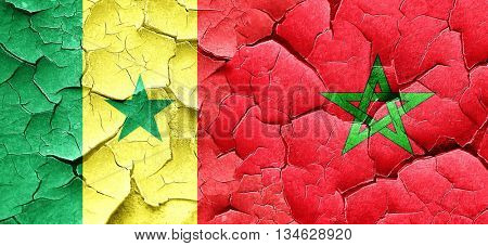 Senegal flag with Morocco flag on a grunge cracked wall