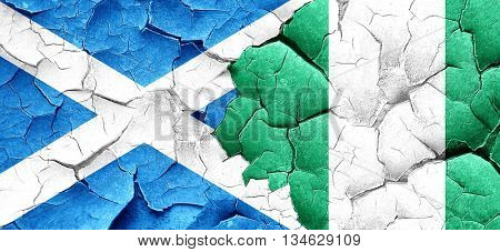 scotland flag with Nigeria flag on a grunge cracked wall