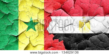 Senegal flag with egypt flag on a grunge cracked wall