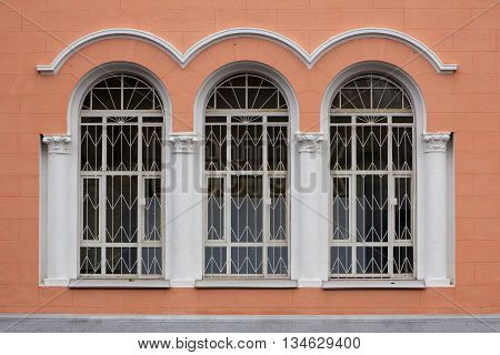 Three arch white windows at stone building